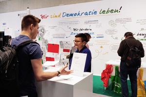 """Eine Mitarbeiterin am Informationsstand des Bundesprogramms beantwortet Fragen eines interessierten Besuchers über Projekte und Inhalte von """"Demokratie leben!"""". Bild: BAFzA"""