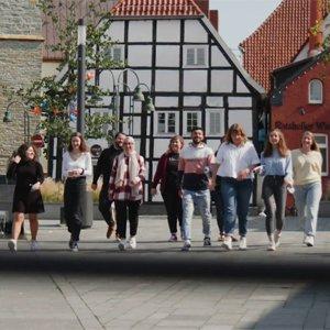Eine Gruppe von Jugendlichen geht über einen Marktplatz