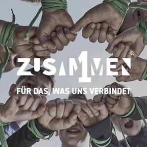 """Foto mit Schriftzug: Mehrere Jugendliche stehen im Kreis. Die Kamera fotografiert aus der Mitte heraus nach oben die zusammenhaltenden Hände der jungen Menschen. In der Bildmitte steht """"Zusammen1 – Für das, was uns verbindet""""."""