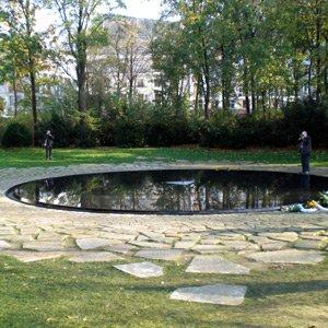 Ein kreisrundes Wasserbecken in einer Wiese