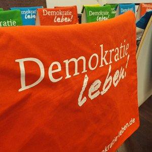 Ein Stoffbeutel mit dem Schriftzug Demokratie leben! hängt über einer Stuhllehne